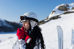 Female Skier Warming Hands on Sunny Mountainside. Head and Shoulders Close Up of Young Woman with Long Dark Hair Wearing Helmet and Goggles Standing on Snowy Royalty Free Stock Photos