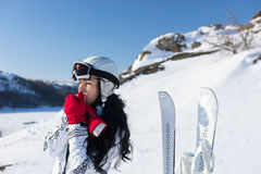 Female Skier Warming Hands on Sunny Mountainside. Waist Up of Young Woman with Long Dark Hair Wearing Ski Goggles and Helmet Standing Next to Skis and Warming Stock Photo