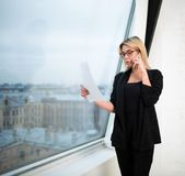 Female skilled manager holding paper documents and calling with cellphone stock photo