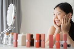 Female Skin Care. Young asian woman touching her face and looking to mirror. stock images