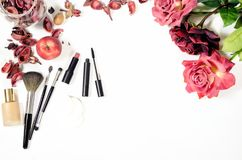 Beauty flatlay make up items. Female skincare flatlay composition with with women items: make up brushes, flowers and petals royalty free stock images