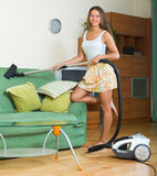 Female  in skirt cleaning with vacuum cleaner Royalty Free Stock Photo