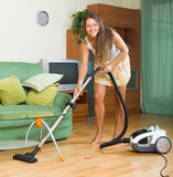 Female in skirt cleaning with vacuum cleaner Royalty Free Stock Photos