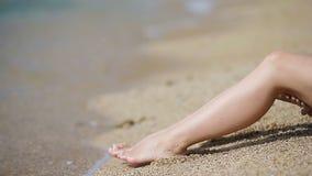 Female slender smooth legs on white sand beach stock video footage
