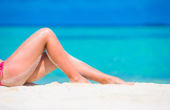Female slim tanned legs on a white tropical beach Royalty Free Stock Photography