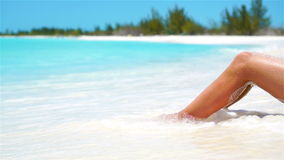 Female slim tanned legs on a white tropical beach. SLOW VIDEO. Female tanned slim legs on the white sandy tropical beach stock footage