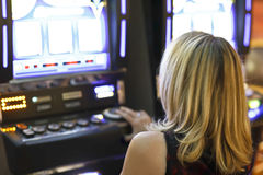 Female slot machine gambler Stock Image