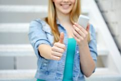 Female with smartphone showing thumbs up Stock Photo
