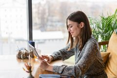 Female smile. Young woman Typing on tablet, chatting, maintains a blog. Freelancer work in cafe modern coworking royalty free stock image