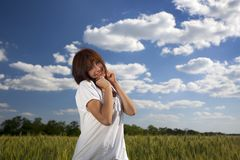 Female smiling against blue sky and wheat fie Stock Photo