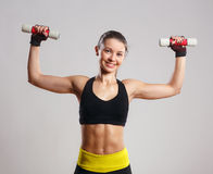 Female Smiling Fitness Model with dumbbells Royalty Free Stock Image