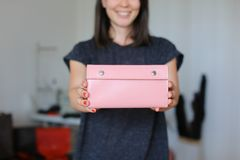 Female smiling person standing with pink leather handmade wallet at home atelier. Concept of handicraft goods Royalty Free Stock Images