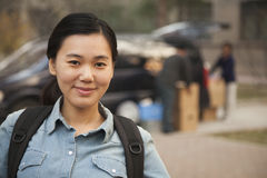 Female smiling student portrait in front of dormitory at college stock photo