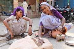 Female Snake Charmer. A female snake charmer and young boy with severe burns sit in the blistering heat, a difficult job for sure Stock Photo