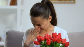Female sniffing red flowers bouquet aroma and sneezing suffering allergy, health. Stock footage stock video