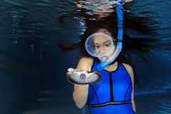 Female snorkeler and shell. Female snorkeler underwater with sea shell and pearl Royalty Free Stock Image