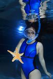 Female snorkeler and starfish. Female snorkeler underwater with starfish Stock Images