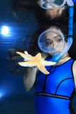 Female snorkeler and starfish Royalty Free Stock Photography