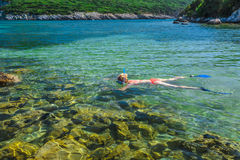 Female snorkeler in tropical sea. Young caucasian female bikini snorkeling in beautiful crystal waters of famous Voidokilia Beach in Peloponnese, Greece. Woman Stock Photos