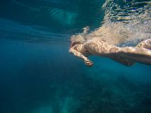 Young woman swimming and snorkeling with mask and fins in clear blue water stock photo