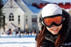 Female snowboarder. Caucasian female snowboarder wearing  goggles, smiling, looking at viewer, lying in snow on mountain with ski resort in background Royalty Free Stock Image