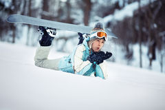 Female snowboarder blowing snow Stock Images