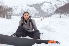 Female snowboarder with braids is seated on the fresh snowy gro. Brunette female snowboarder with braids is seated on the fresh snowy ground, close to the ski royalty free stock photo