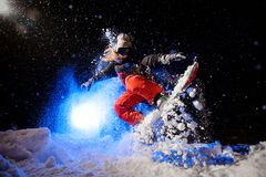 Female snowboarder dressed in a orange sportswear jumping on the mountain slope. In the night under the blue light royalty free stock images
