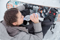 Female snowboarder is drinking for quenching the thirst. Female snowboarder is resting on a snowy ground while she is drinking water for quenching the thirst royalty free stock photography