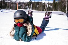 Female snowboarder lying on a snowy slope. Relax. royalty free stock photos