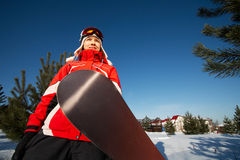 Female snowboarder over blue sky in forest Stock Images