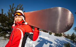 Female snowboarder over blue sky in forest Royalty Free Stock Photo