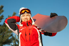 Female snowboarder over blue sky in forest Royalty Free Stock Photos