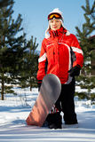 Female snowboarder over blue sky in forest Stock Image