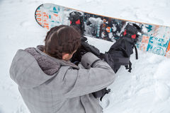 Female snowboarder is searching stuff inside the backpack. Brunette female snowboarder with beautiful braids, is searching some stuff inside her backpack, while royalty free stock photography