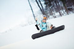 Female snowboarder showing thumb up Royalty Free Stock Photography