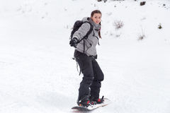 Female snowboarder is skiing. An engrossed beginner female snowboarder girl is skiing with her snowboard on a ski backcountry slope with fresh snow condition stock photos