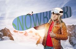 Female snowboarder with snowboard in front of a wintry mountain landscape Royalty Free Stock Photo