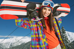 Female snowboarder on top of the mountain Royalty Free Stock Photos