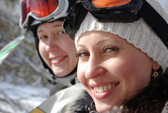 Female snowboarders. Two smiling female snowboarders on a chairlift Royalty Free Stock Image