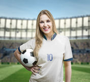 Female soccer fan on white and blue uniform in the stadium Stock Photo