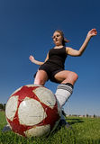Female soccer kick. A female soccer player kicking the ball, main focus on the ball Royalty Free Stock Images