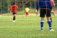 Female soccer match. Where the goalkeeper is keeping watch and some players are in the distance.  Netting visible in foreground Royalty Free Stock Image