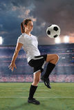 Female Soccer Player Dribbling Ball. Young female soccer player dribbling ball inside stadium royalty free stock images