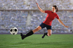 Female Soccer Player Going for Ball. Beautiful female soccer player sliding to reach ball inside stadium stock photos