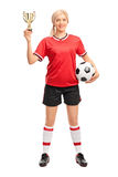 Female soccer player holding a golden trophy Royalty Free Stock Photography