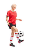 Female soccer player juggling a ball and smiling Royalty Free Stock Images