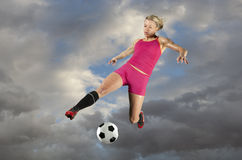 Female Soccer Player Kicking a Ball Royalty Free Stock Photos