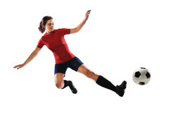 Female Soccer Player Kicking Ball. Beautiful female soccer player sliding to kick ball isolated over white background stock photos