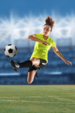 Female Soccer Player Kicking Ball. In large stadium stock images